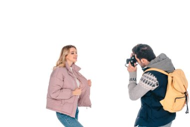 man with backpack holding camera and photographing beautiful girlfriend isolated on white