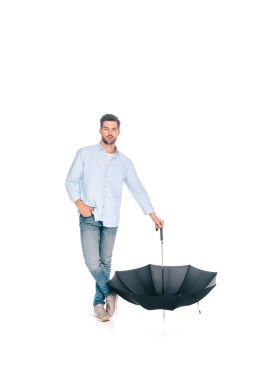 full length view of handsome man holding black umbrella and looking at camera isolated on white