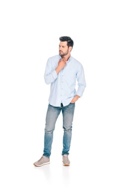full length view of handsome young man standing with hand in pocket and looking away isolated on white