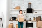 Fotografia giovane donna sorpresa guardando nella scatola di cartone in cucina a casa nuova