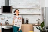 Fotografie lächelnde junge Frau am Smartphone beim Umzug in neues Zuhause