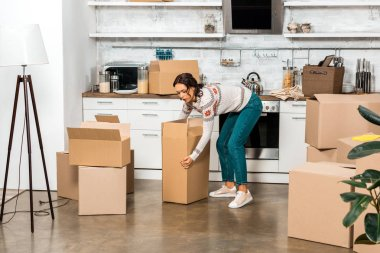 young woman taking cardboard box during relocation in new home