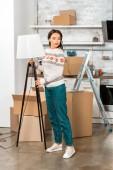 fiatal nő elhelyezés lámpa konyhában során áthelyezése az új haza