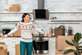 Fotografie laughing young woman doing shrug gesture in kitchen with cardboard boxes during relocation in new home