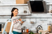 Fotografie attractive smiling woman holding candles in kitchen near ladder during relocation at new home