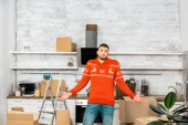 Fotografie young man doing shrug gesture in kitchen with cardboard boxes during relocation in new home