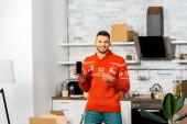 happy young man pointing by finger at smartphone with blank screen in kitchen with cardboard boxes during relocation in new home