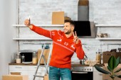 happy young man doing peace sign and taking selfie on smartphone in kitchen with cardboard boxes during relocation in new home