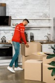 Fotografie rear view of man taking cardboard box in kitchen during relocation at new home