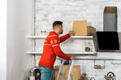 rear view of man standing on ladder and putting cardboard box on shelf in kitchen during relocation in new home