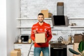 smiling man with cardboard box in kitchen with cardboard boxes during relocation in new home