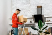 Photo side view of man standing on ladder with cardboard box in kitchen during relocation in new home