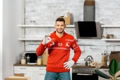 Fotografie happy young man in working gloves doing ok sign gesture in kitchen with cardboard boxes during relocation in new home