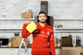 Fotografie emotional young man holding yellow dirty rag in kitchen during relocation at new home