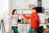 izgatott fiatal pár ünneplő áthelyezése az új haza, és a konyhában pezsgő szemüveg csengő