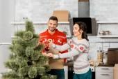 Fotografie šťastný mladý pár zdobení vánočního stromku od cetky v kuchyni doma