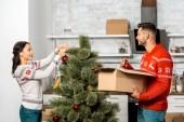 usmíval se mladý pár, zdobení vánočního stromku ozdoby v kuchyni doma