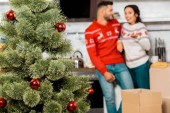 selective focus of christmas tree with baubles and couple standing behind at home