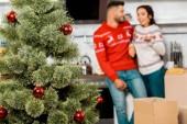Selektivní fokus vánočního stromu s cetky a pár stojící za doma