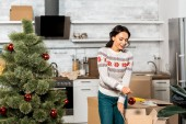 Fotografie happy young woman decorating christmas tree by baubles in kitchen at home