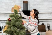 s úsměvem mladá žena, zdobení vánočního stromku ozdoby v kuchyni doma