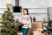 krásná mladá žena, zdobení vánočního stromku ozdoby v kuchyni doma