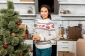 pezsgős üveg konyha otthon a karácsonyfa közelében álló, vonzó nő