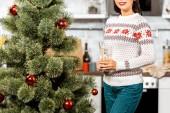 Teilbild einer Frau, die mit Champagnerglas neben dem Weihnachtsbaum in der heimischen Küche steht
