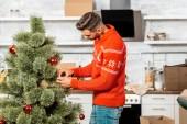 Selektivní fokus člověka zdobení vánočního stromku ozdoby v kuchyni doma
