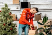 young man decorating christmas tree by baubles in kitchen at home