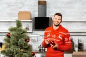 Veselý pohledný muž, zdobení vánočního stromku ozdoby doma