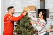 side view of happy young couple decorating christmas tree at home