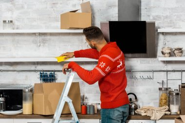 rear view of man standing on ladder and wiping dust from shelves during relocation at new home
