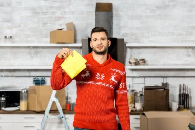 emotional young man holding yellow dirty rag in kitchen during relocation at new home