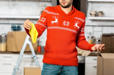 young man holding yellow dirty rag and doing shrug gesture in kitchen during relocation at new home