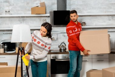 attractive young woman wiping dust from lamp while her boyfriend carrying cardboard box in kitchen at new home