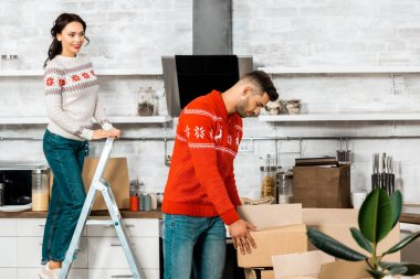 Handsome young man taking cardboard box while his girlfriend standing on ladder behind in new home stock vector
