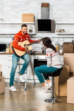 smiling man playing on acoustic guitar to girlfriend sitting in kitchen of new home