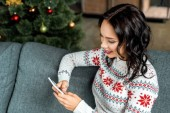 usmívající se žena pomocí smartphone na gauči u vánoční stromeček doma