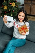 Photo smiling woman taking selfie on smartphone with gift box on sofa near christmas tree at home