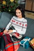 kanapé takaró alatt ül, díszdobozok, otthon a karácsonyfa közelében, a gyönyörű fiatal nő