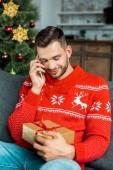 mosolygó ember beszél a smartphone és a gazdaság a kanapé közelében karácsonyfa ajándék doboz otthon