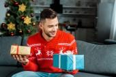 usměvavý mladý muž sedí na pohovce a držení dárkové krabice vánoční stromeček doma