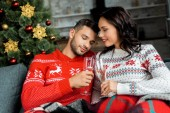Fotografie couple ceebrating and clinking by champagne glasses on sofa near christmas tree at home
