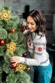 Fotografie glückliche junge Frau schmücken Weihnachtsbaum mit Kugeln zu Hause