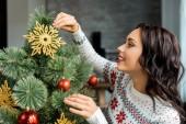 oldalnézet, vonzó nő, otthon a karácsonyfa díszítése