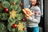 částečný pohled mladé ženy držící krabičky poblíž vánoční stromeček doma