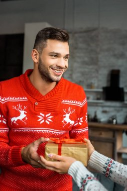 smiling young man gifting christmas present box to girlfriend at home