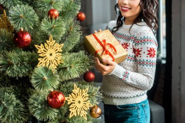 partial view of young woman holding gift box near christmas tree at home