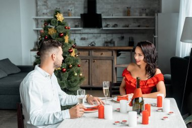 couple celebrating christmas with champagne glasses at served table with candles at home